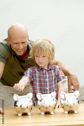 Father and son putting coin in piggy bank, Den Haag, Netherlands