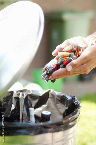 Person putting handful of batteries in garbage can, close-up, Den Haag, Netherlands