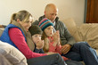 Family in winter clothes keeping warm together on sofa