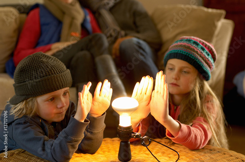 Family in winter clothes warming hands with a light bulb