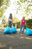 Rear view of two children dragging bags of garbage