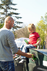Father and son outdoors recycling bottles