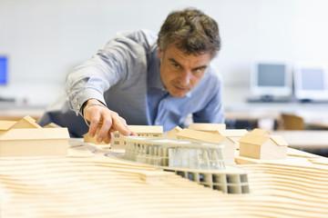 Mature man scrutinizing an architectural model