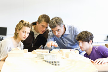 Mature man and teens gathered around an architectural model