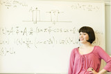 Smiling young woman posing before equation written on board
