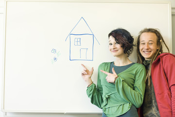 Two teenagers smiling at one another before a drawing of a house