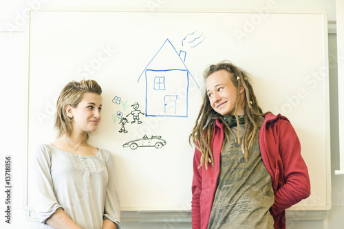 Two teenagers smiling in front of a drawing of a house