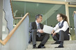 Businessmen sitting at top of staircase with laptop