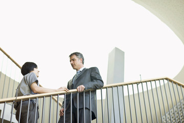 Businessmen standing at top of staircase having discussion