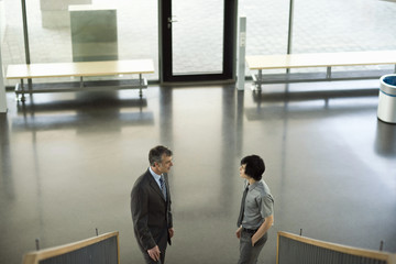Businessmen standing at bottom of staircase having discussion