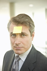 Portrait of mature man with note paper stuck on forehead