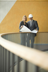 Two mature adults standing on balcony of building with plans