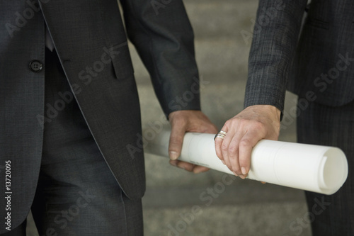Close-up of two hands holding rolled up paper