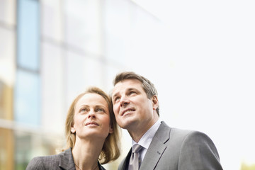 Mature couple in business suits gazing upward in Munich, Bavaria, Germany
