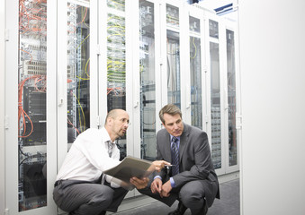 Two mature men crouching down in a computer server room