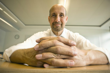 Close-up of clasped hands of mature man sitting at table