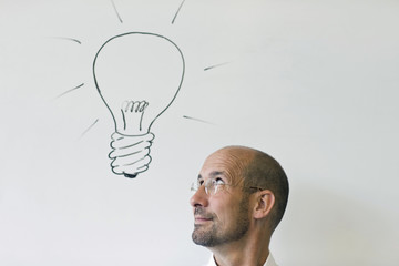 Headshot of mature man looking up at line drawing of light bulb