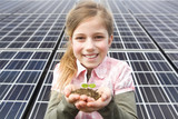 Young girl holding seedling and soil in front of solar panels in Munich, Bavaria, Germany