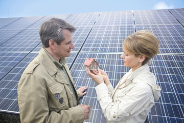 Mature couple standing in front of solar panels holding miniature house in Munich, Bavaria, Germany