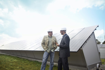 Mature businessmen talking in front of solar paneling, Munich, Germany