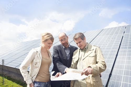 Three mature adults reading plans in front of solar panels in Munich, Bavaria, Germany
