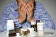 Man surrounded by medicine bottles, studio shot