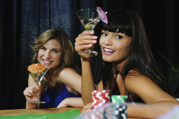 Two young women holding martinis at a poker table