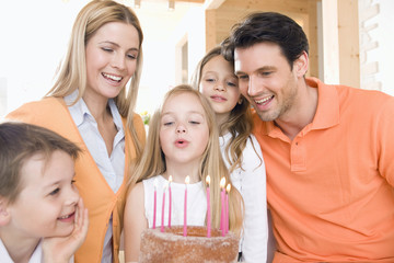 Young girl with family holding birthday cake with lit candles