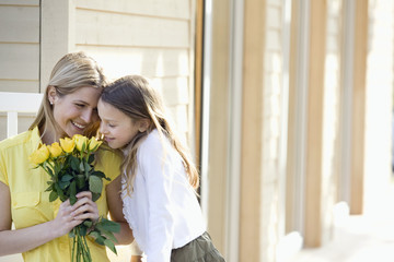 Portrait of mother and daughter smelling a bouquet of yellow roses