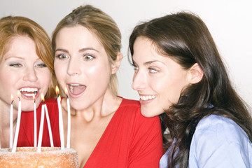 Young woman holding a birthday cake, surrounded by her friends
