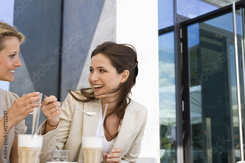 Two women drinking milkshakes at outdoor caf, Stuttgart, Baden-Wurttemberg, Germany