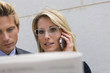 Businesswoman talking on cell phone standing next to businessman, Stuttgart, Baden-Wurttemberg, Germany
