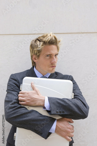Businessman holding files to his chest, Stuttgart, Baden-Wurttemberg, Germany