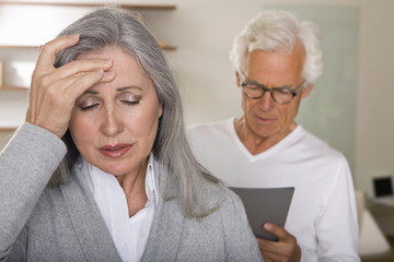 Mature woman with headache, man in background