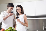 Young couple drinking red wine in kitchen