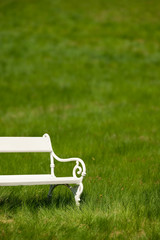 White bench in green meadow