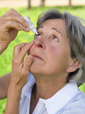 Senior woman using eye drops