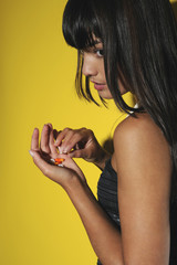Young woman taking pills, studio shot