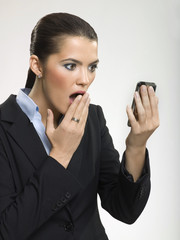 Businesswoman looking at cell phone in shock