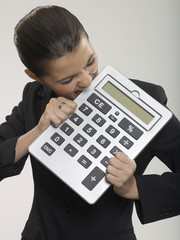 Businesswoman biting large calculator