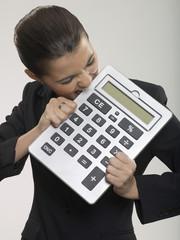 Businesswoman biting large calculator