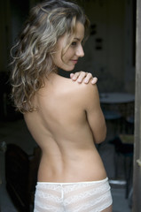 Rear view of young Caucasian topless woman