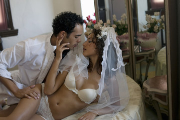 Young multi-ethnic couple in bed on their wedding night