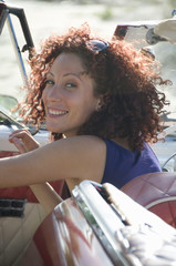 Young woman getting out of car, smiling, close-up, Havana, Cuba