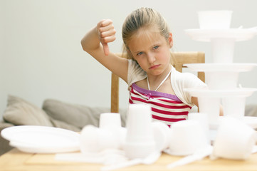 Portrait of girl sitting in front of disposable tableware, showing thumbs down, close-up, Den Haag, Netherlands