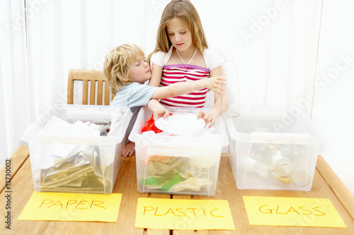 Boy and girl separating paper, plastic and glass, Den Haag, Netherlands