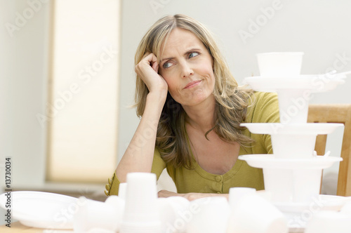 Mature woman sitting in front of disposable tableware, Den Haag, Netherlands