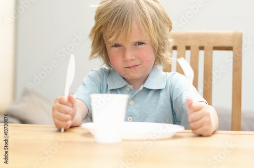 Portrait of boy sitting at table with plastic fork, knife, plate and glass, close-up, Den Haag, Netherlands