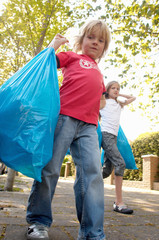 Low angle view of two children carrying trash bags