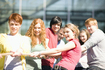 Group of teenagers pulling on rope outdoors
